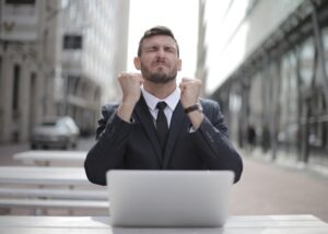 happy man at laptop  for blog by Burnett Mortgages on can a mortgage broker get you a better deal.