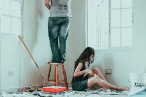Couple decorating their home for blog by Burnett Mortgages on do mortgage brokers charge a fee